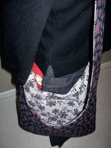 Sling bag with curved base, no gusset. Designed and made by Fiona Ballard, Pip 'n' Milly Creations using Patty Young fabric. Black exterior with pink and grey flowers. Light grey floral lining with vivid pink accent fabric for pockets and key clip. Zippered pocket.