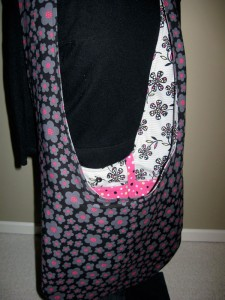 Sling bag in black Patty Young fabric with pink and grey flowers. Vivid pink polka dot accent fabric.