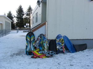 Line up of sleds, snow boards outside portable classroom