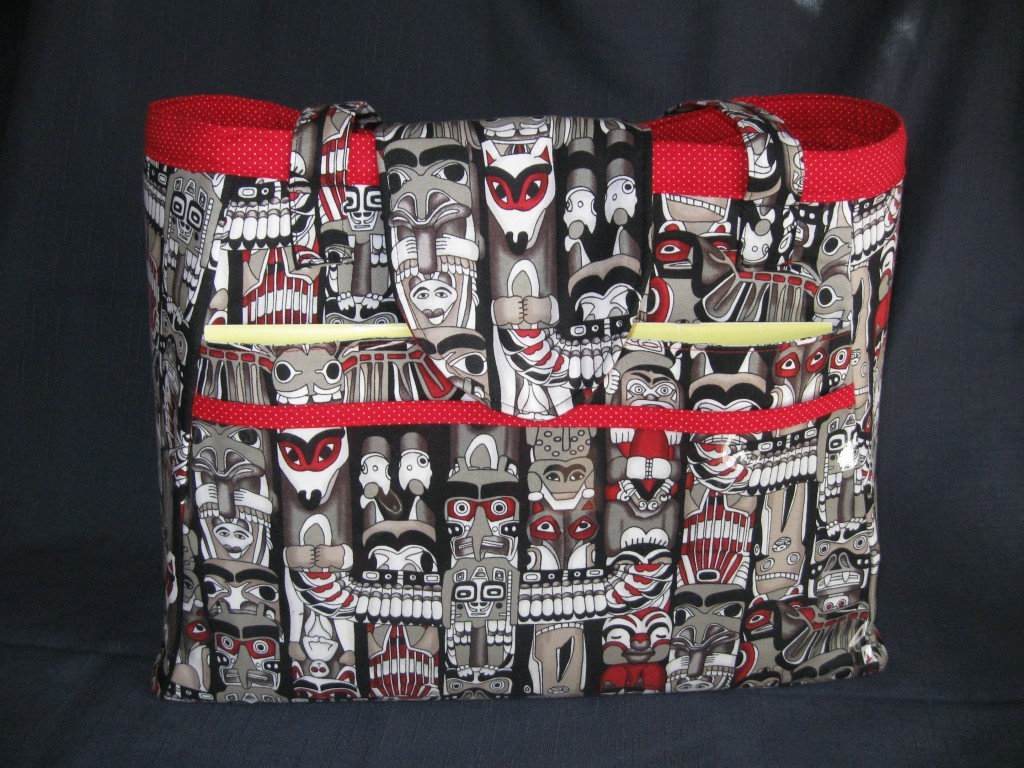 Custom order knitting bag in totem pole fabric, with red polka dot lining. Photos shows clear front pocket, large front pocket with pattern poking out, adjustable flap, shoulder straps and red binding for top of bag and pocket